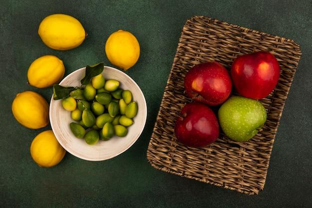 Bovenaanzicht van verse kleurrijke appels op een rieten dienblad met kinkans op een kom met citroenen geïsoleerd op een groen oppervlak