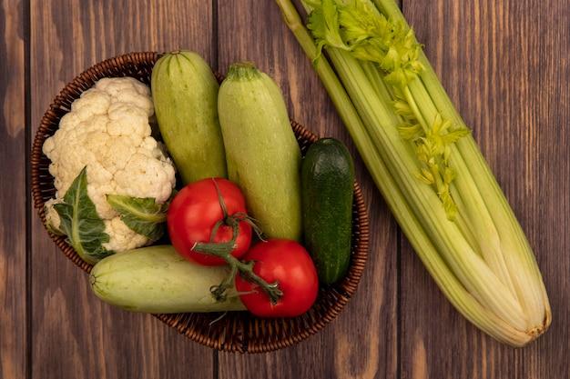 Bovenaanzicht van verse kleurrijke groenten zoals tomaten, courgette, komkommer en bloemkool op een emmer met selderij geïsoleerd op een houten muur