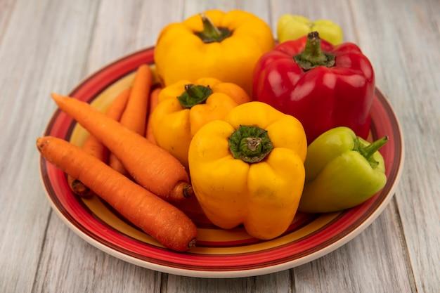 Bovenaanzicht van verse kleurrijke paprika op een bord met wortelen op een grijze houten ondergrond