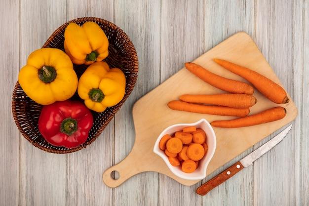 Bovenaanzicht van verse kleurrijke paprika op een emmer met wortelen op een houten keukenplank met mes op een grijze houten achtergrond