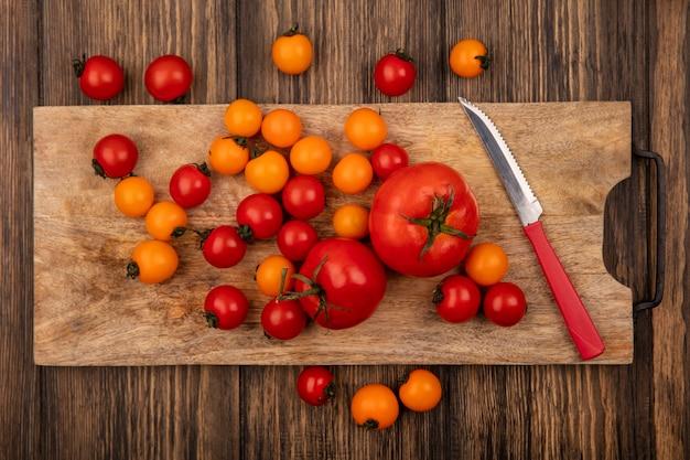Bovenaanzicht van verse kleurrijke tomaten geïsoleerd op een houten keukenbord met mes op een houten oppervlak