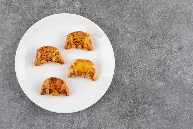 Bovenaanzicht van verse koekjes op witte plaat.