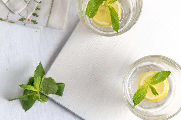 Bovenaanzicht van verse koele limonade met gesneden citroenen in glazen op lichtwit oppervlak