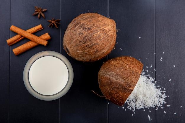Bovenaanzicht van verse kokosnoten met kaneelstokje met een glas melk met een poeder van kokosnoot op hout