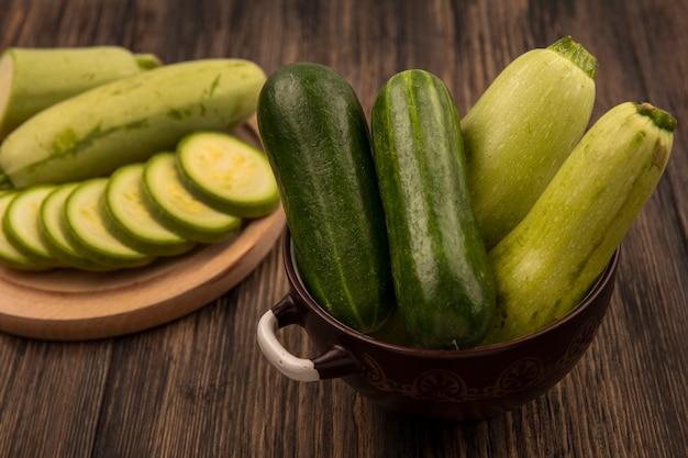 Bovenaanzicht van verse komkommers op een kom met gehakte courgettes op een houten keukenbord op een houten muur