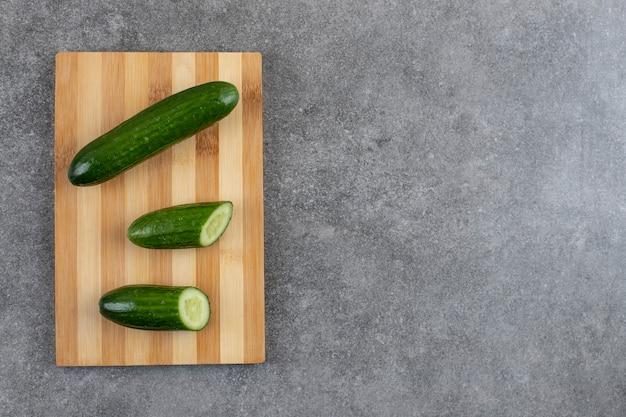 Bovenaanzicht van verse komkommers op houten snijstaaf.