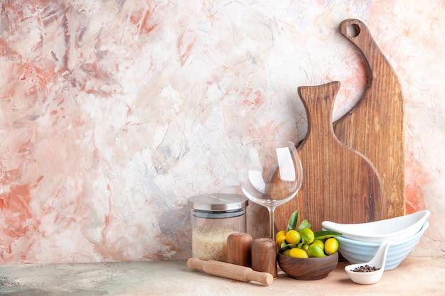 Bovenaanzicht van verse kumquats gestapelde potten houten snijplanken glazen beker rijst op kleurrijk oppervlak