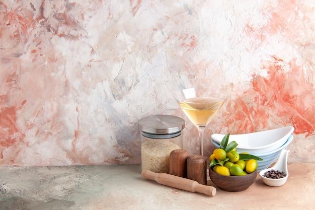Bovenaanzicht van verse kumquats gestapelde potten wijn in glazen beker rijst op kleurrijke ondergrond