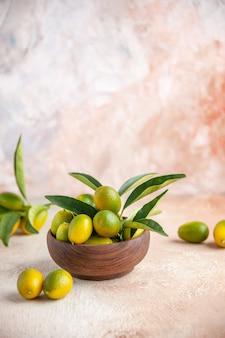 Bovenaanzicht van verse kumquats met stengels binnen en buiten kleine houten pot op kleurrijke ondergrond