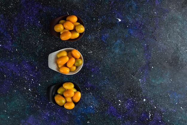 Bovenaanzicht van verse kumquats op blauwe ondergrond