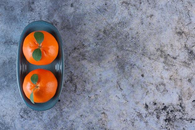 Bovenaanzicht van verse mandarijnen met bladeren op grijze plaat.