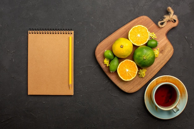 Bovenaanzicht van verse mandarijnen met feijoa en kopje thee op zwart