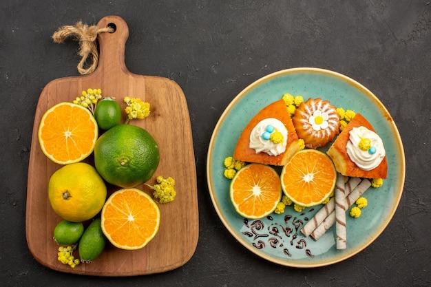 Bovenaanzicht van verse mandarijnen met feijoa en plakjes cake op zwart
