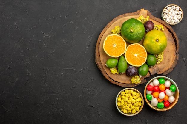 Bovenaanzicht van verse mandarijnen met feijoa en snoepjes op zwart