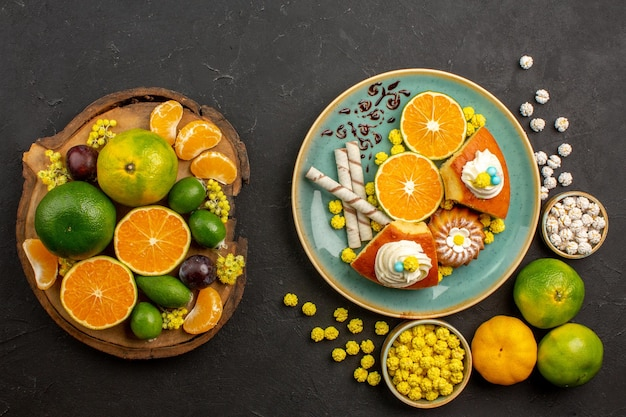 Bovenaanzicht van verse mandarijnen met feijoa en taart op zwart