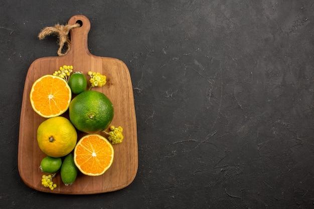 Bovenaanzicht van verse mandarijnen met feijoa op zwart