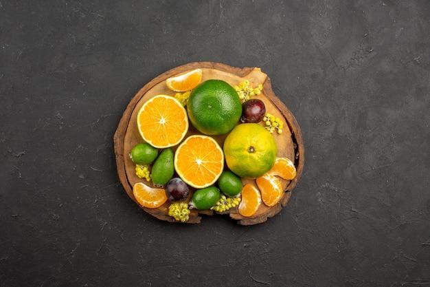 Bovenaanzicht van verse mandarijnen met feijoa's op zwart
