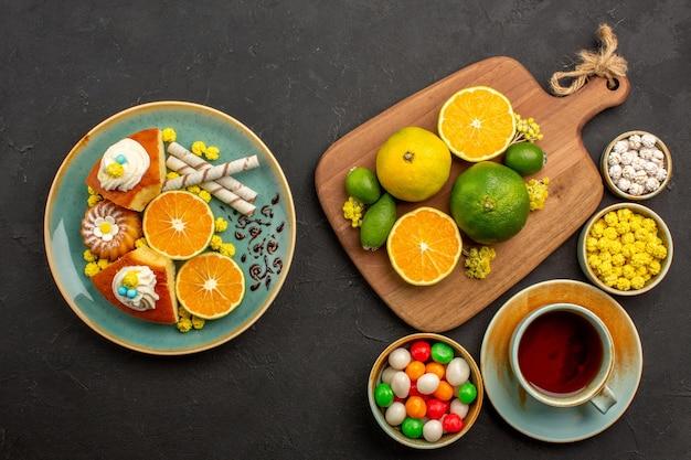 Bovenaanzicht van verse mandarijnen met kopje thee en snoep op zwart