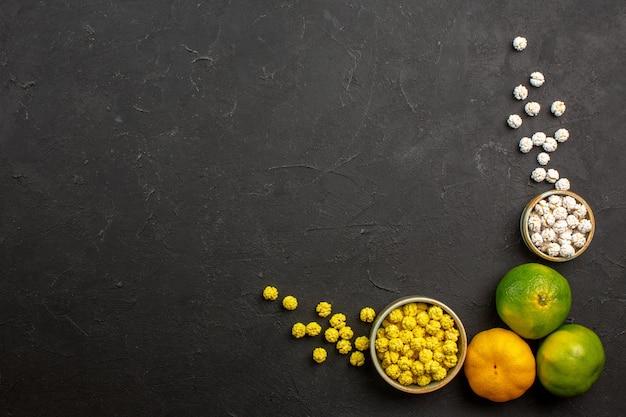 Bovenaanzicht van verse mandarijnen met snoepjes op grijze tafel