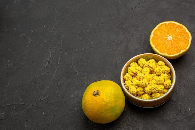Bovenaanzicht van verse mandarijnen met snoepjes op zwarte tafel