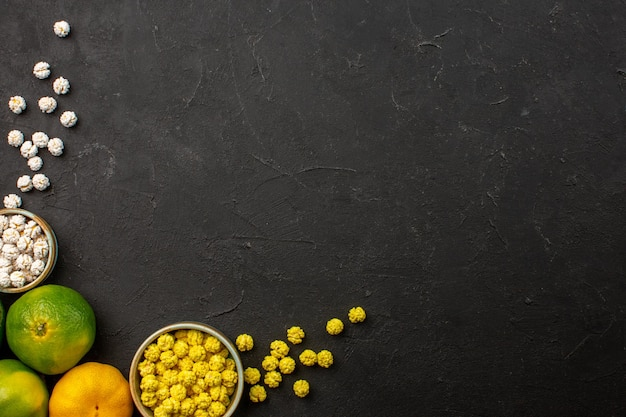 Bovenaanzicht van verse mandarijnen met snoepjes op zwartgrijsgre