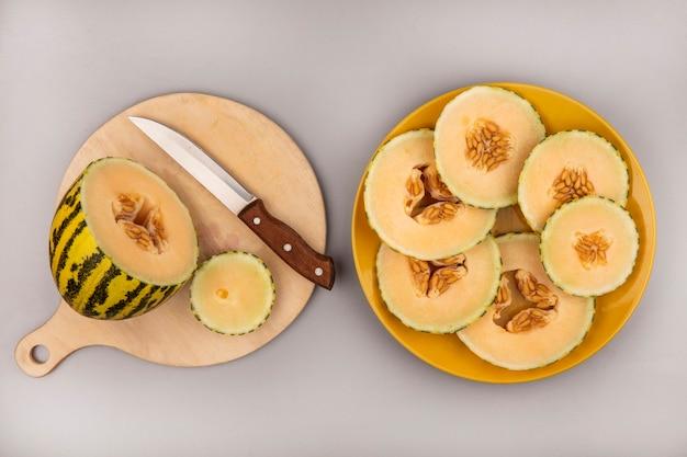 Bovenaanzicht van verse meloen meloen op een houten keukenplank met mes met plakjes meloen op een gele plaat op een witte muur