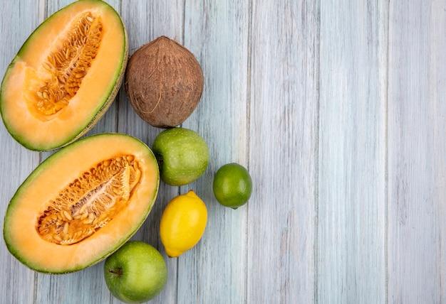 Bovenaanzicht van verse meloen plakjes meloen met kokos citroenen op grijs met kopie ruimte