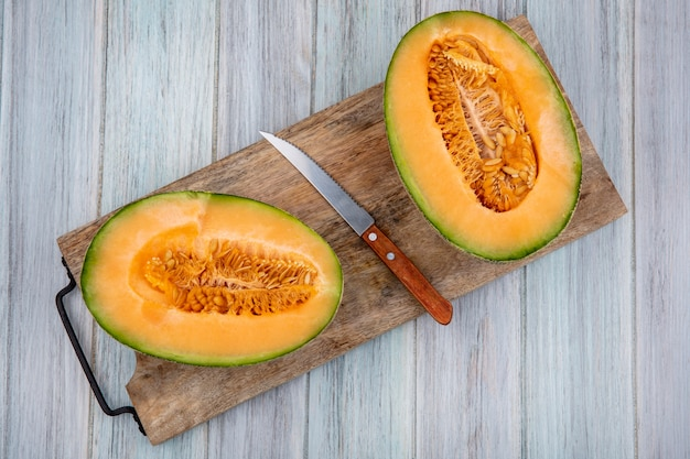 Bovenaanzicht van verse meloen plakjes meloen op houten keukenbord met mes op grijs hout