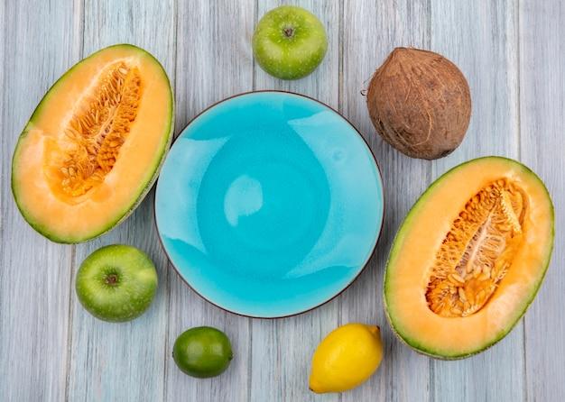 Bovenaanzicht van verse meloen plakjes met kokos groene appels op grijs met kopie ruimte