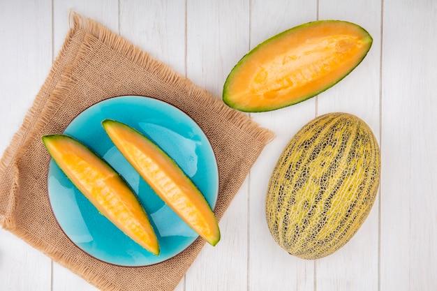 Bovenaanzicht van verse meloenen op blauw bord op zakdoek met plakjes op wit