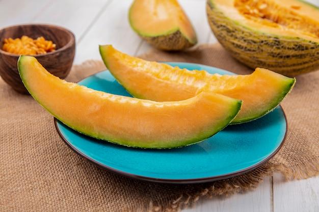 Bovenaanzicht van verse meloenen op blauw bord op zakdoek met zaden op houten kom op wit