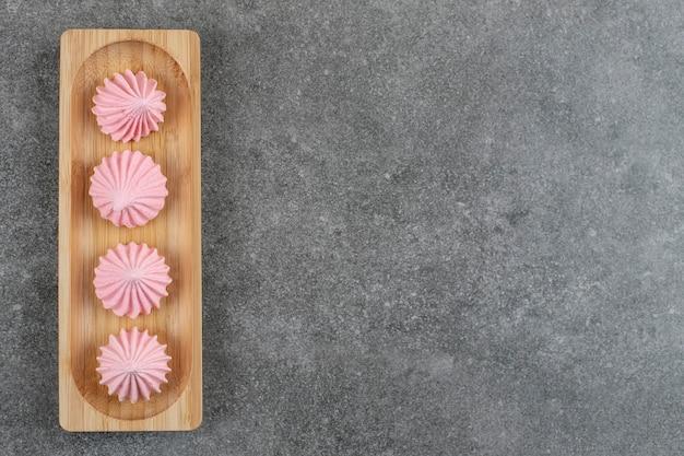 Bovenaanzicht van verse meringue cookies op een houten bord