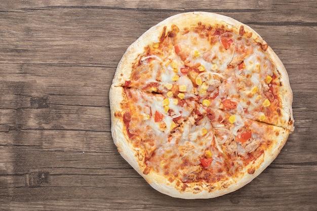 Bovenaanzicht van verse mozzarella pizza op houten tafel.
