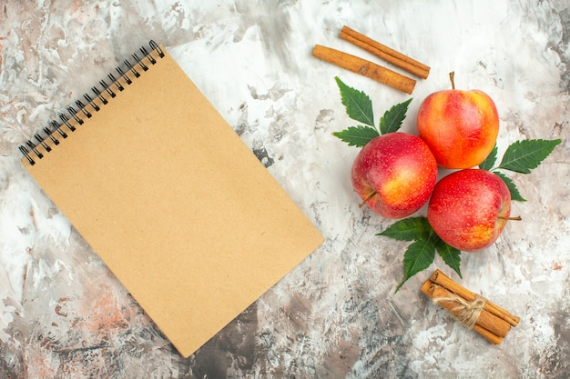 Bovenaanzicht van verse natuurlijke rode appels en kaneellimoenen en spiraalvormig notitieboekje op gemengde kleurenachtergrond