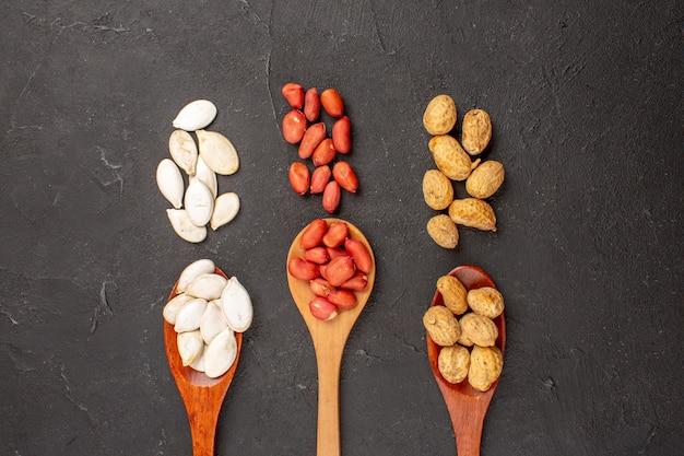 Bovenaanzicht van verse noten, pinda's en andere noten op donkere ondergrond
