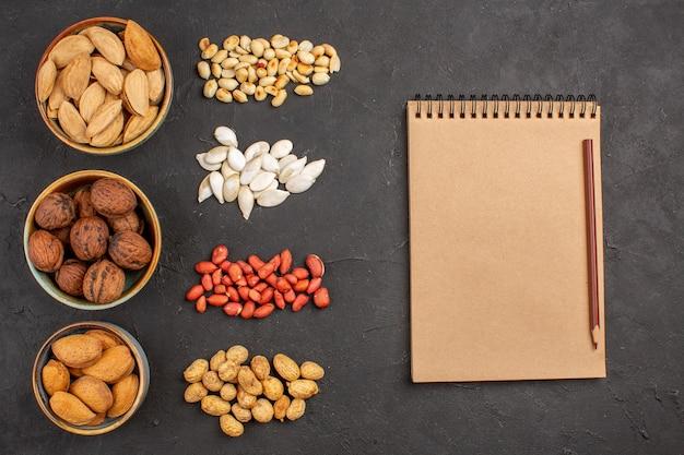 Bovenaanzicht van verse noten, pinda's en andere noten op grijze ondergrond