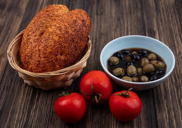 Bovenaanzicht van verse olijven op een blauwe kom met pasteitjes op een emmer met tomaten geïsoleerd op een houten achtergrond