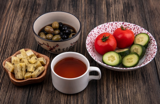 Bovenaanzicht van verse olijven op een boog met groenten met een kopje groenblauw op een houten achtergrond