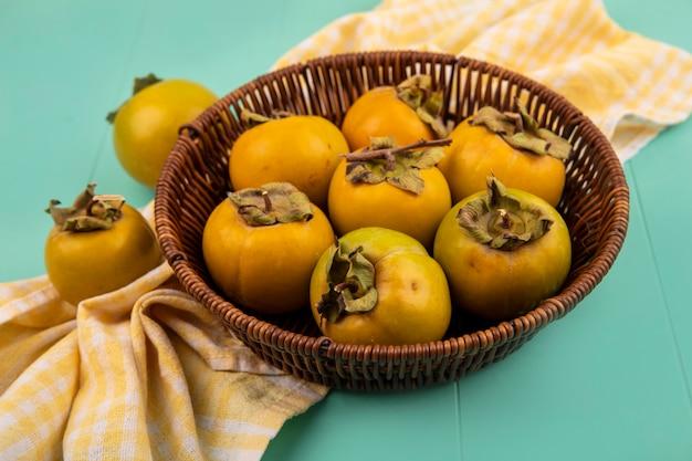 Bovenaanzicht van verse onrijpe kaki fruit op een emmer op een geel geruit doek op een blauwe houten tafel