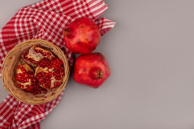 Bovenaanzicht van verse open granaatappels op een emmer op een gecontroleerde doek met kopie ruimte