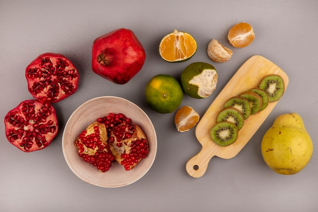 Bovenaanzicht van verse open granaatappels op een kom met plakjes kiwi op een houten keukenbord met kweeperen en mandarijnen geïsoleerd