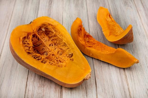 Bovenaanzicht van verse oranje halve pompoen met plakjes geïsoleerd op een grijze houten oppervlak