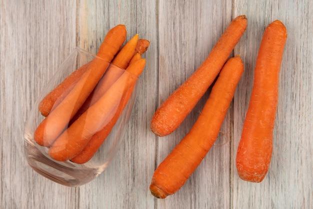Bovenaanzicht van verse oranje wortelen op een glas met wortelen geïsoleerd op een grijze houten achtergrond