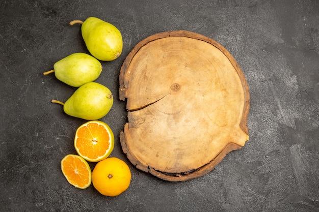 Bovenaanzicht van verse peren met mandarijnen op zwartgrijsgre