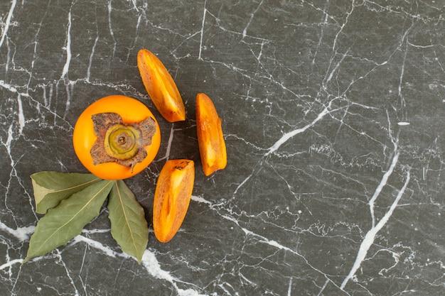 Bovenaanzicht van verse persimmon. geheel of in plakjes met bladeren.