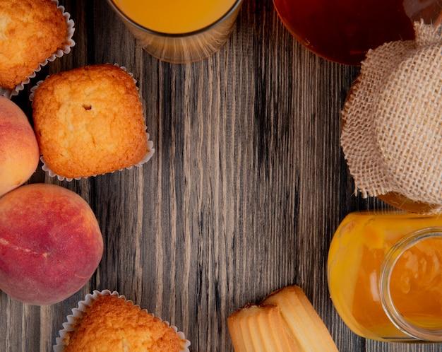 Bovenaanzicht van verse perziken met muffins, koekjes, glas perziksap en perzikjam in een glazen pot op rustiek hout met kopie ruimte