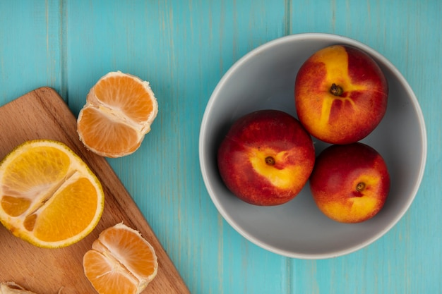 Bovenaanzicht van verse perziken op een kom met mandarijnen op een houten keukenbord op een blauwe houten muur