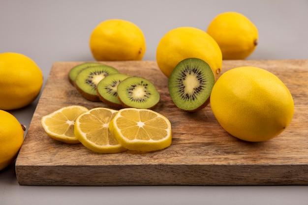 Bovenaanzicht van verse plakjes citroen en kiwi geïsoleerd op een houten keukenbord op een grijze achtergrond