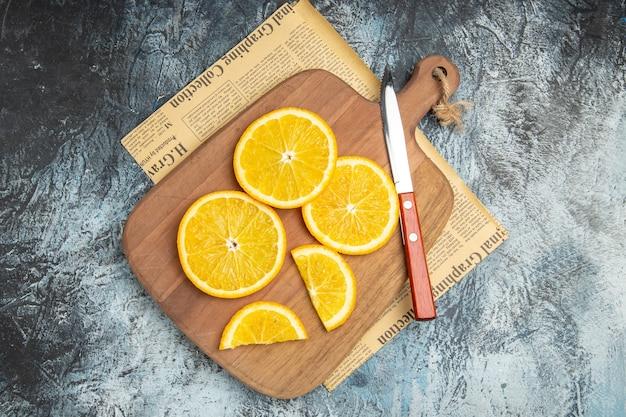 Bovenaanzicht van verse plakjes citroen met mes op houten snijplank op krant op grijze achtergrond