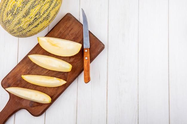 Bovenaanzicht van verse plakjes meloenen op houten keukenbord met mes op wit hout